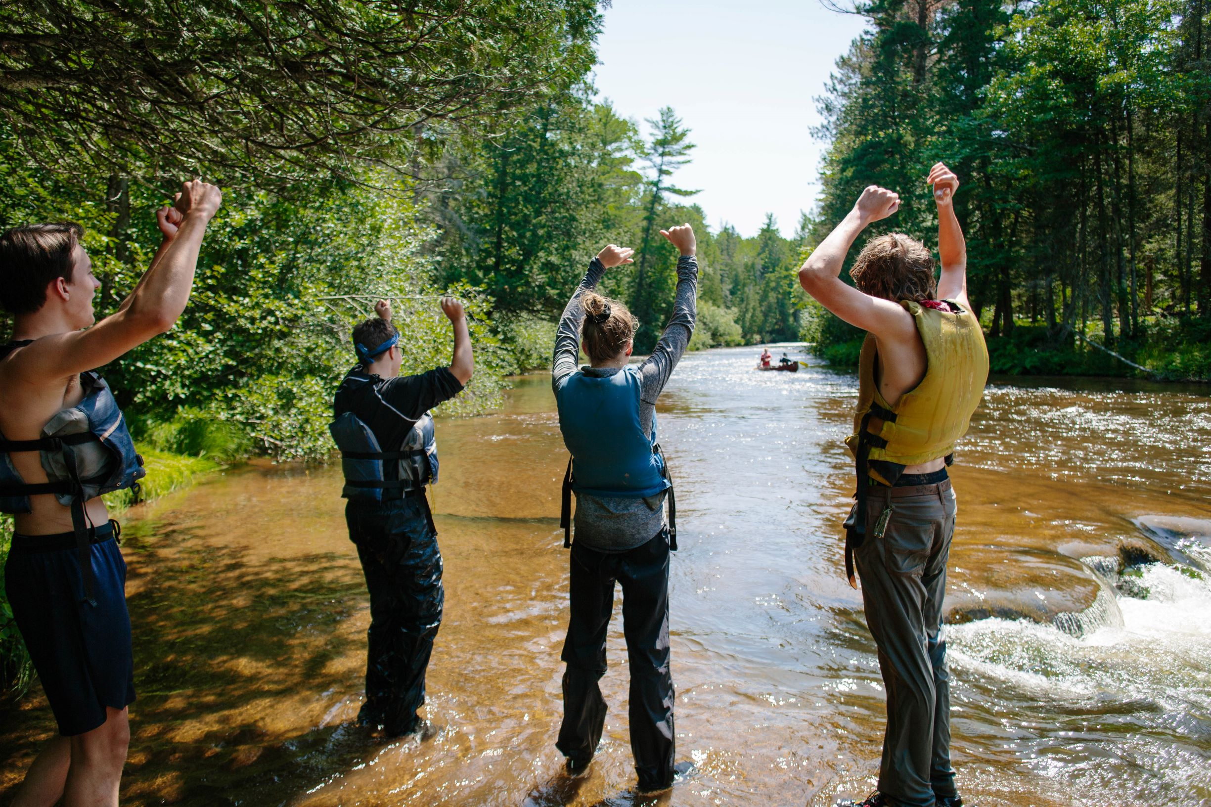 A team of women work together to pull a 35' Montreal Canoe onto shore in the Apostle Islands